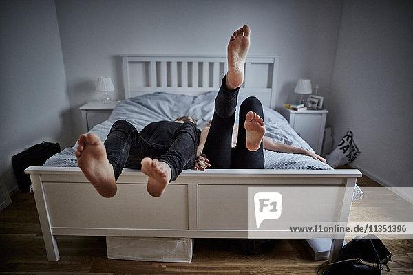 Füße eines Paares im Bett