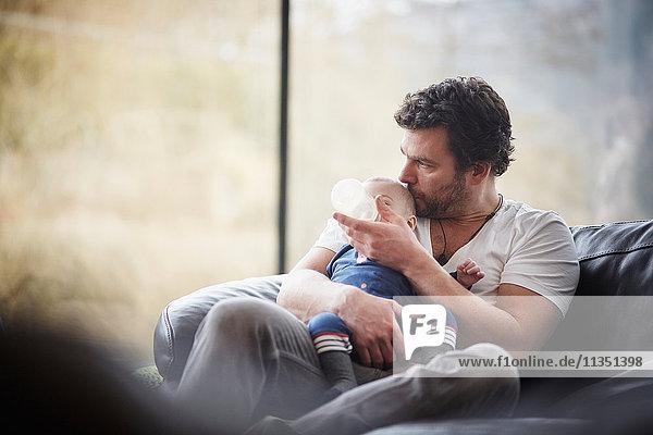 Vater gibt seinem Baby das Fläschchen auf der Couch