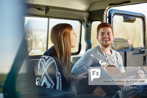 Fröhliches junges Paar macht Musik in einem Auto