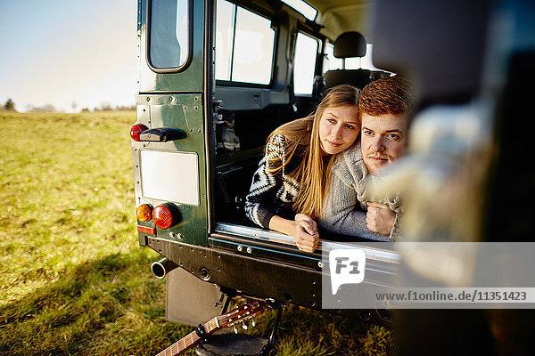 Junges Paar liegt im Auto geparkt auf einer Wiese