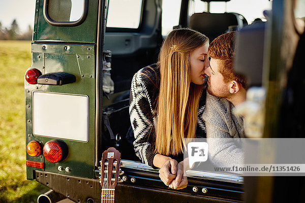 Junges Paar küsst sich in einem Auto