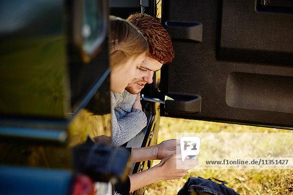 Junges Paar liegt im Auto und schaut auf ein Handy