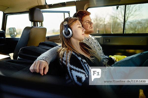 Entspanntes junges Paar mit Kopfhörern und Schlafsack in einem Auto