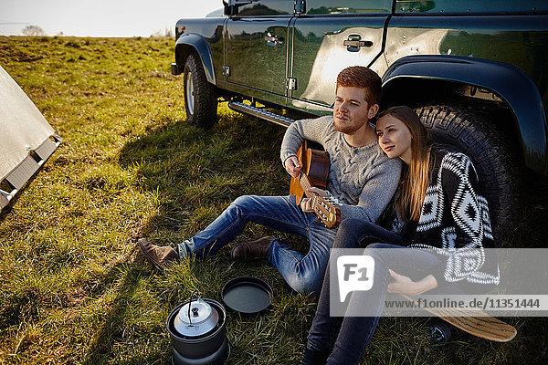 Junges Paar sitzt auf einer Wiese neben einem Auto und macht Musik