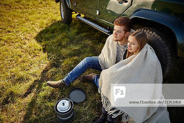 Junges Paar sitzt auf einer Wiese neben einem Auto und Campingkocher
