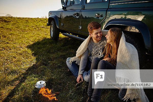 Glückliches junges Paar sitzt auf einer Wiese neben einem Auto und Campingkocher