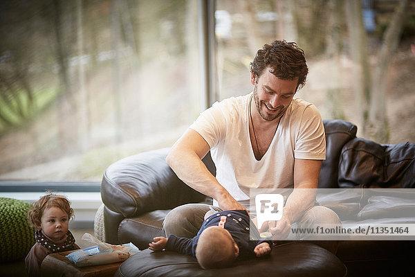 Vater mit Tochter wechselt die Windeln seines Babies im Wohnzimmer