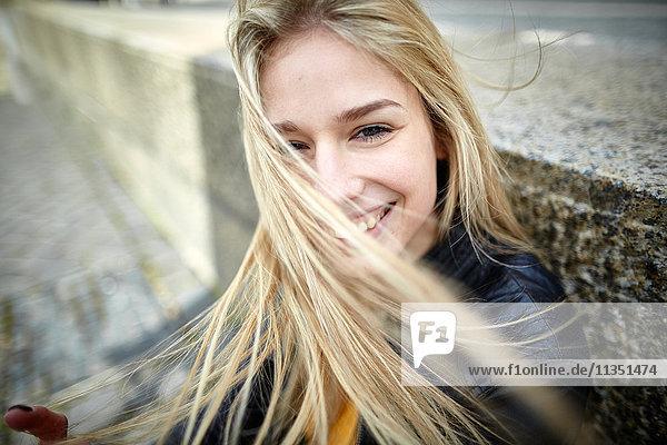 Portrait einer lächelnden jungen Frau mitwehendem Haar