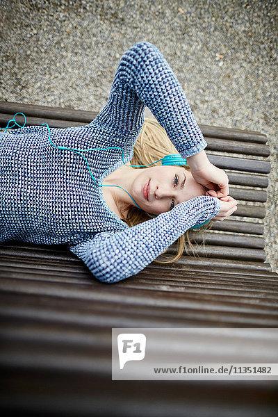 Junge Frau mit Kopfhörern liegt auf einer Bank