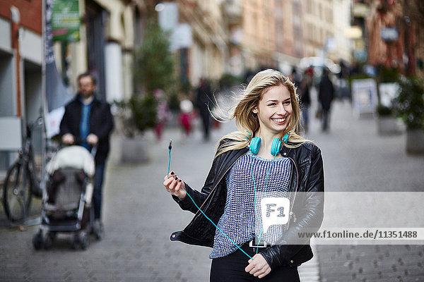 Fröhliche junge Frau mit Kopfhörern in der Fußgängerzone