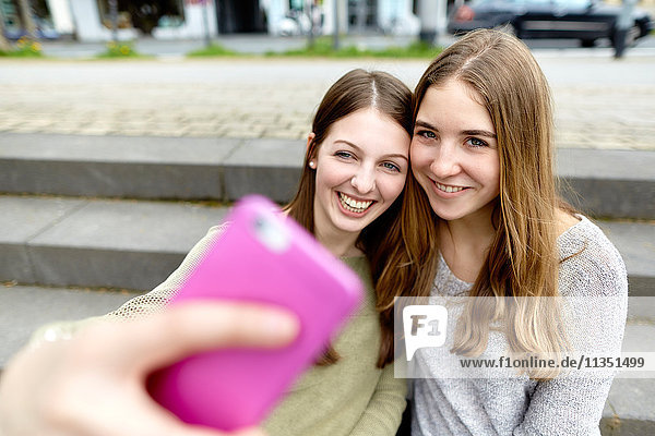 Zwei lächelnde junge Frauen machen ein Selfie