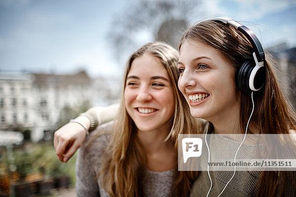 Glückliche junge Frau mit Freundin trägt Kopfhörer