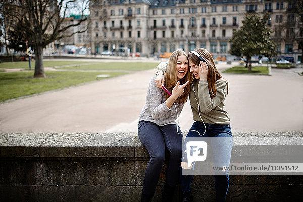 Lachende junge Frau mit Freundin trägt Kopfhörer