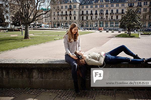 Entspannte junge Frau mit Kopfhörern liegt auf dem Schoß ihrer Freundin