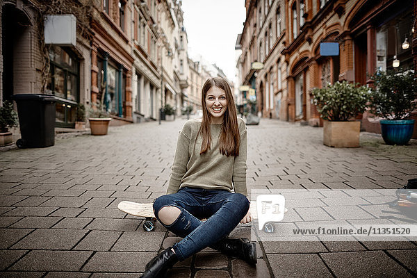 Portrait of smiling young woman sitting on skateboard in the city