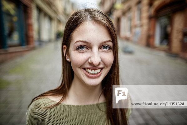 Portrait einer lächelnden jungen Frau in der Stadt
