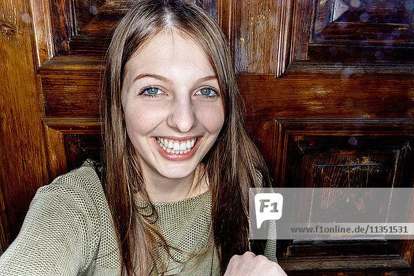 Portrait einer lächelnden jungen Frau vor einer Holztür
