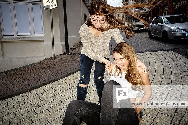 Zwei fröhliche junge Frauen mit Skateboard in der Stadt