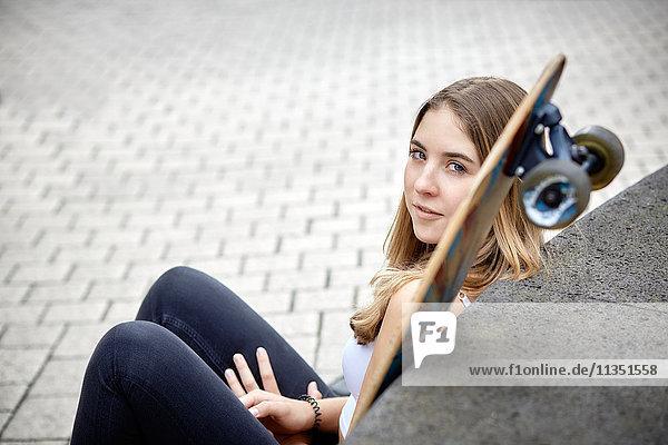 Sitzende junge Frau mit Skateboard