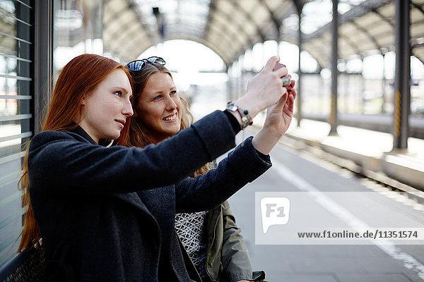 Zwei junge Frauen machen ein Selfie auf dem Bahnsteig