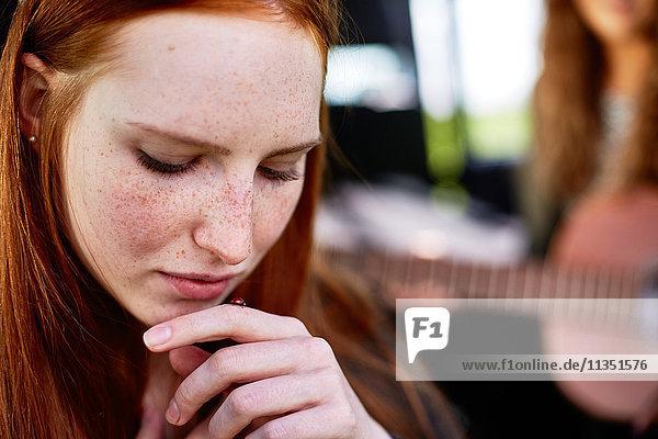 Junge Frau schaut auf einen Marienkäfer auf ihrem Finger