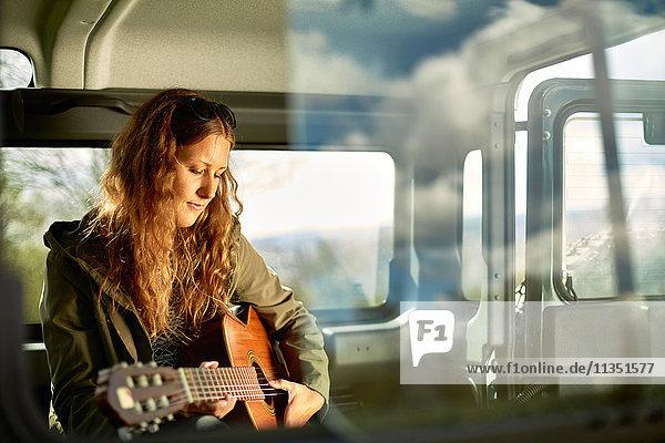 Junge Frau spielt Gitarre im Auto