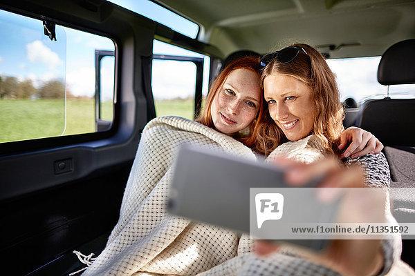 Zwei junge Frauen machen ein Selfie im Auto