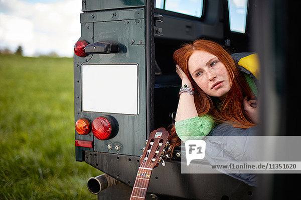 Junge Frau mit Schlafsack liegt in einem Geländewagen auf einer Wiese