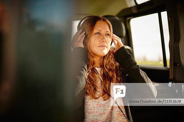 Junge Frau im Auto hört Musik mit Kopfhörern