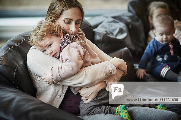 Mutter tröstet Tochter auf der Couch mit Geschwistern im Hintergrund