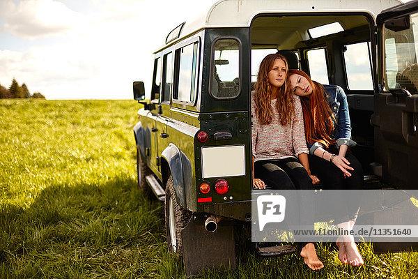 Zwei junge Frauen sitzen im Kofferraum eines Geländewagens auf einer Wiese