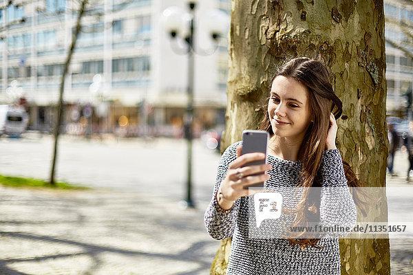 Lächelnde Teenagerin mit Handy an einem Baum