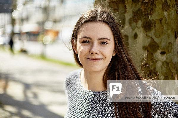 Portrait einer lächelnden Teenagerin an einem Baum
