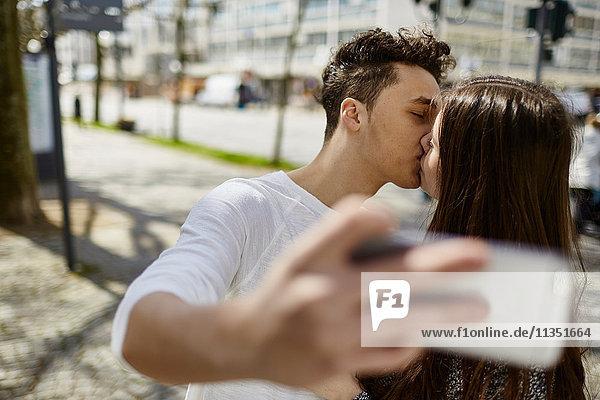 Verliebtes Teenagerpaar küsst sich und macht ein Selfie