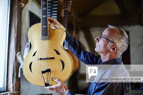 Gitarrenbauer untersucht eine E-Gitarre in seiner Werkstatt