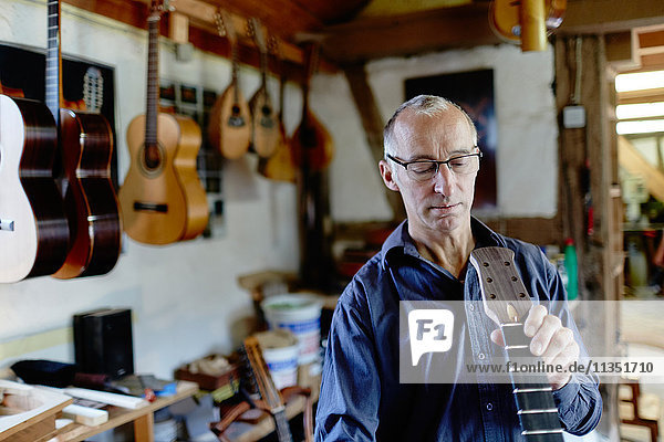 Gitarrenbauer untersucht eine Gitarre in seiner Werkstatt