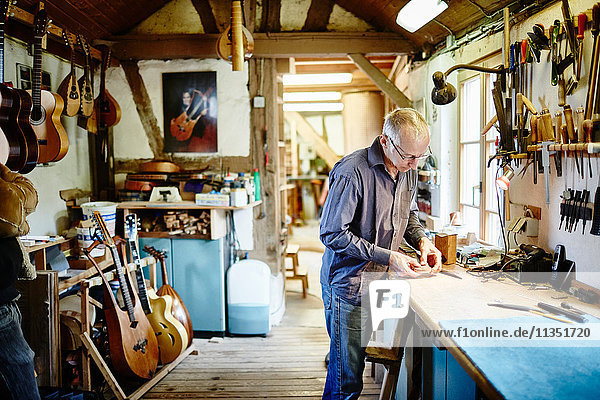 Guitar maker in his workshop at work