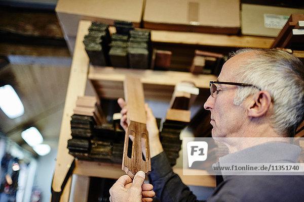 Gitarrenbauer untersucht ein Griffbrett in seiner Werkstatt