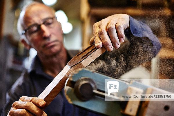 Gitarrenbauer schleift ein Griffbrett in seiner Werkstatt