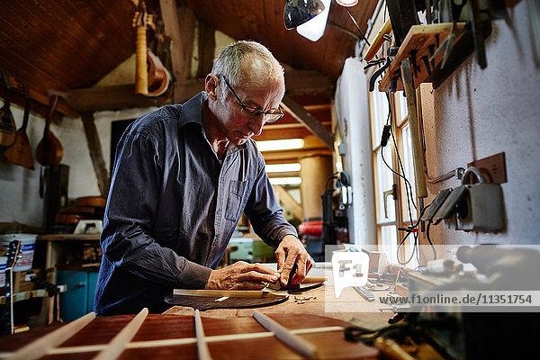 Gitarrenbauer arbeitet in seiner Werkstatt