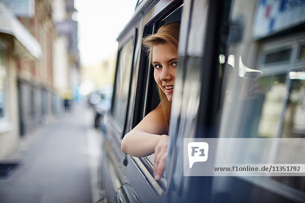 Young woman in car looking out of window