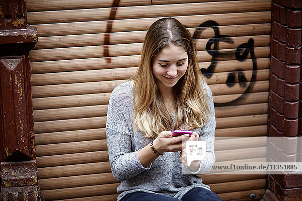 Lächelnde junge Frau sitzt auf der Türschwelle und schaut auf ihr Handy