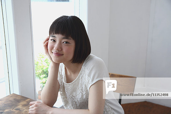 Young Japanese woman sitting at a wooden table in airy room