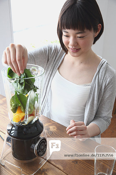 Young Japanese woman preparing juice in airy room