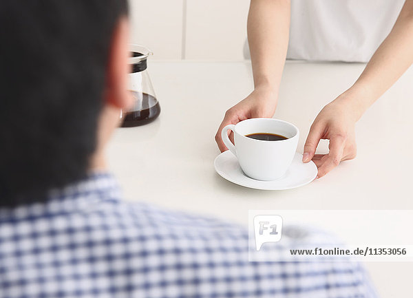 Japanese man getting coffee from woman in the kitchen