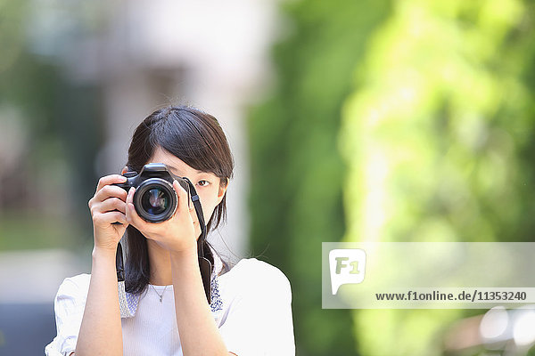 Young Japanese woman taking pictures with DSLR