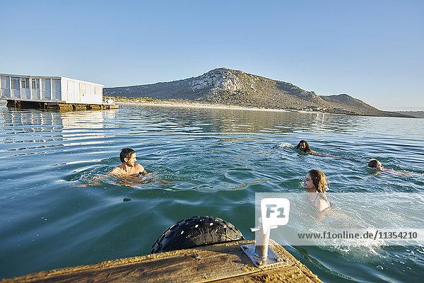 Junge erwachsene Freunde schwimmen im sonnigen Sommermeer