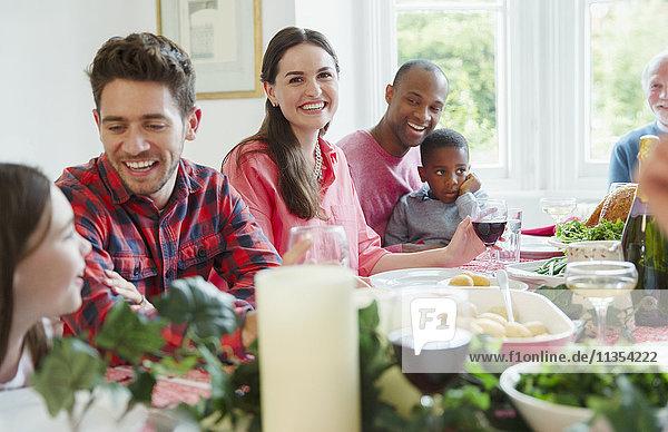 Portrait lächelnde Frau beim Weihnachtsessen mit der Familie am Tisch