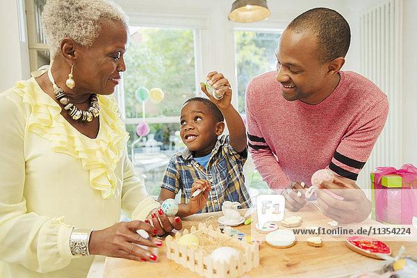 Mehrgenerationen-Familie dekoriert Ostereier und Kekse in der Küche