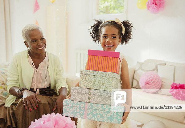 Portrait lächelndes Mädchen mit einem Stapel Geburtstagsgeschenke